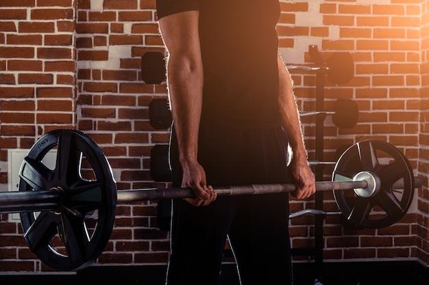 Homem musculoso e em forma, fazendo exercícios de bíceps com halteres no ginásio, copie o espaço.