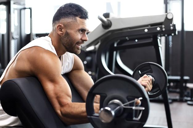 Homem musculoso e em forma, levantando peso de barra pesada usando o banco no ginásio.