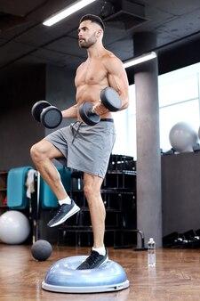 Homem musculoso e em forma, malhando com sinos na bola de bosu do hemisfério de ginástica no ginásio.