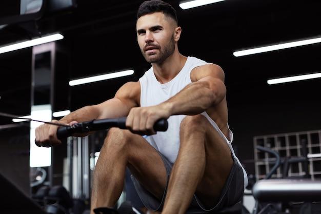 Homem musculoso e em forma usando máquina de remo no ginásio.