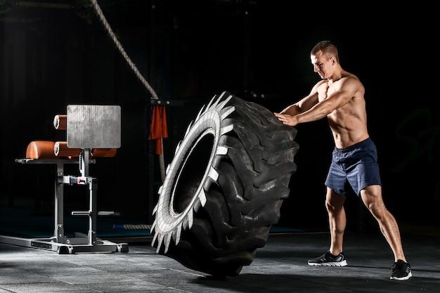 Homem musculoso e esportivo lançando um pneu pesado na academia