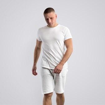 Homem musculoso e magro em uma camiseta em branco e shorts cinza de malha em um fundo branco do estúdio. pose frontal. o modelo pode ser usado em seu design.