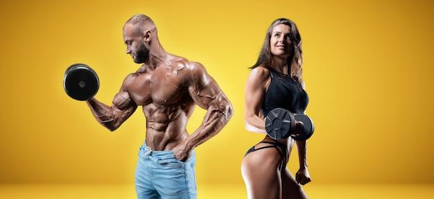 Homem musculoso e mulher posando com halteres em um fundo amarelo. conceito de musculação e fitness. mídia mista