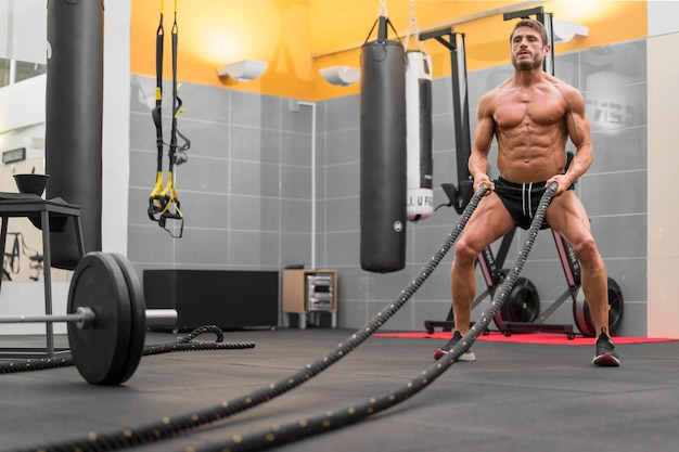 Homem musculoso e poderoso malhando com corda em uma academia de ginástica de treinamento funcional