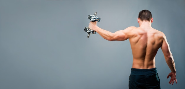 Homem musculoso em fundo cinza