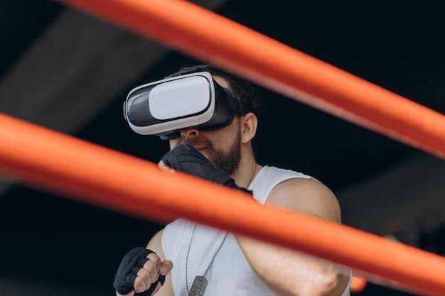 Homem musculoso em óculos de realidade virtual e luvas de boxe, dando socos em direção à câmera