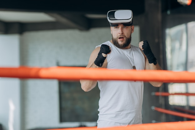 Homem musculoso em óculos de realidade virtual e luvas de boxe