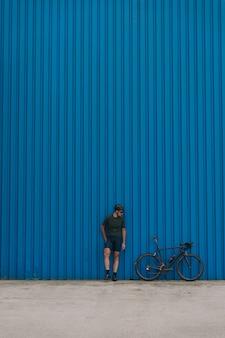 Homem musculoso em pé perto de uma parede azul com uma bicicleta preta