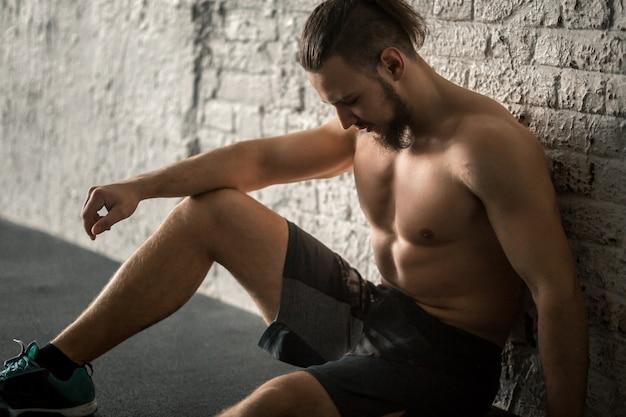 Homem musculoso em repouso após treino de ginásio