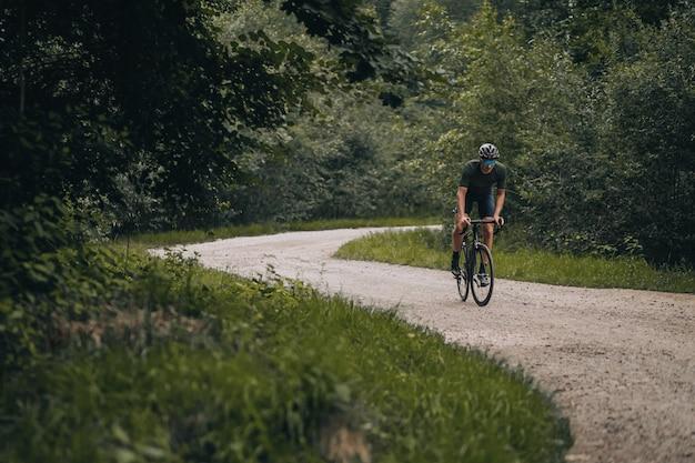 Homem musculoso em roupas esportivas andando de bicicleta na trilha