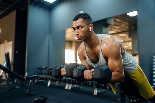 Homem musculoso em roupas esportivas, fazendo exercícios com halteres no banco, treinando na academia