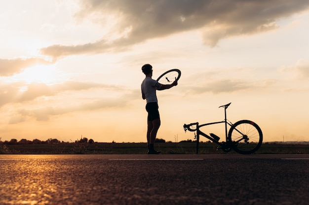 Homem musculoso em silhueta consertando a roda de uma bicicleta quebrada em fresco