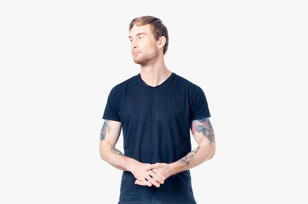Homem musculoso em uma camiseta azul com tatuagens nos braços em uma visão recortada de fundo claro