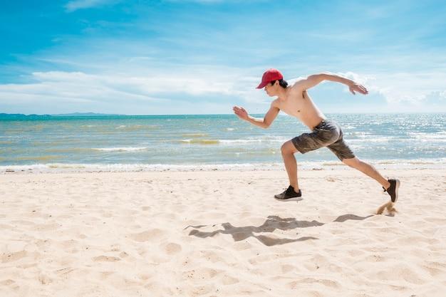 Homem musculoso está correndo na praia
