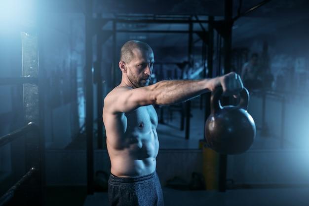Homem musculoso exercícios com kettlebell em treinamento