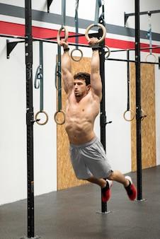 Homem musculoso exercitando em anéis