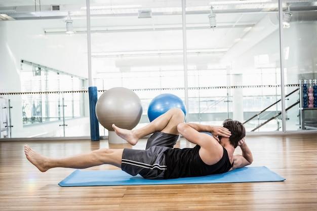 Homem musculoso fazendo abdominal na esteira no estúdio