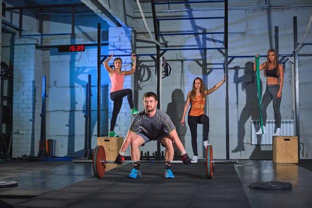 Homem musculoso fazendo agachamentos com barra em uma academia