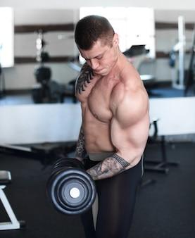 Homem musculoso, fazendo exercícios com halteres no bíceps. força e motivação.