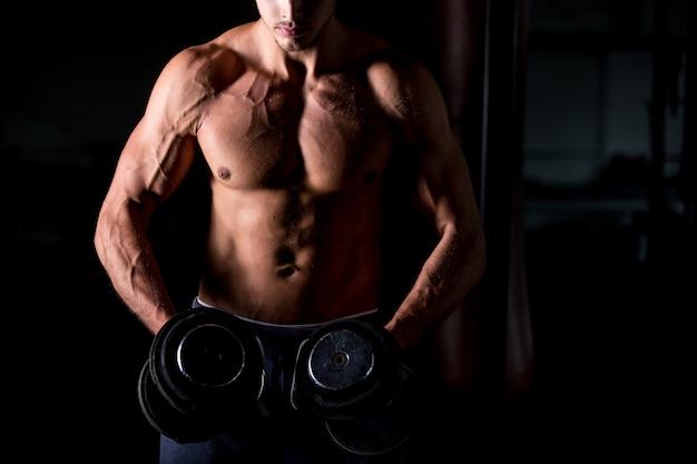 Homem musculoso fazendo exercícios com halteres no centro de fitness