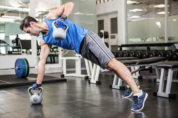 Homem musculoso fazendo exercícios com kettlebells no ginásio