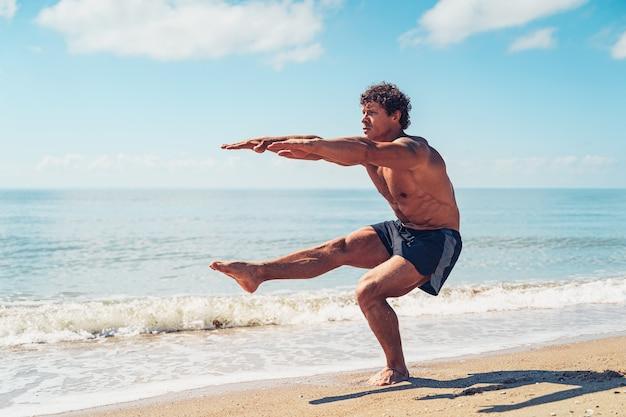 Homem musculoso fazendo exercícios em musculação na praia