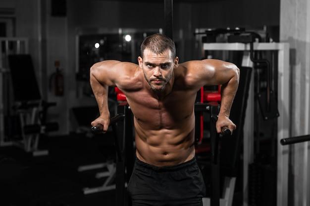 Homem musculoso fazendo flexões em barras assimétricas no ginásio crossfit.