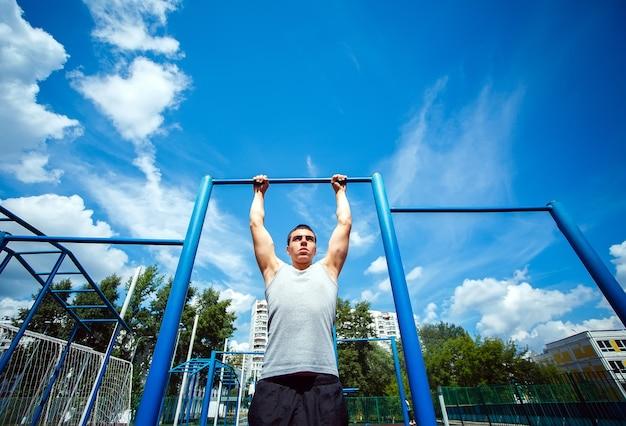 Homem musculoso fazendo flexões na barra horizontal