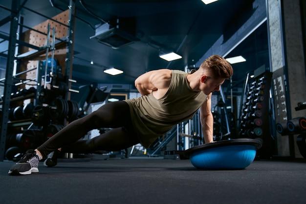 Homem musculoso fazendo flexões por um lado.