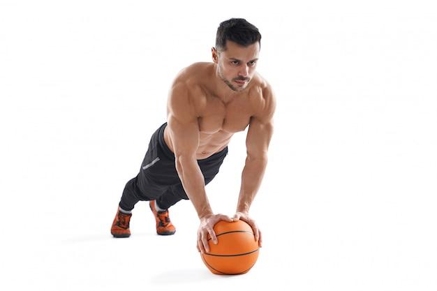 Homem musculoso fazendo flexões usando basquete.