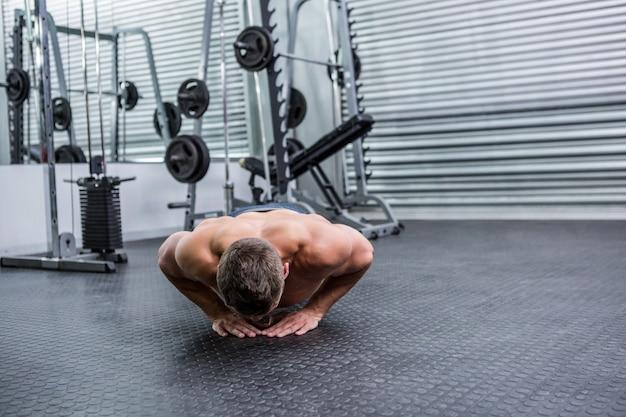 Homem musculoso fazendo flexões