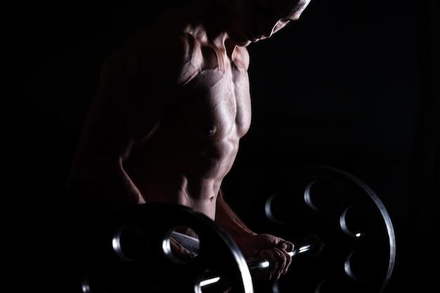 Homem musculoso fazendo levantamento de peso no centro de fitness