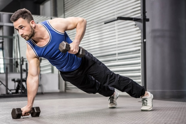 Homem musculoso fazendo push-up com halteres no ginásio crossfit