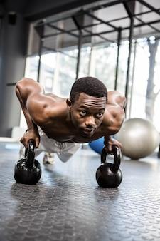 Homem musculoso fazendo push-up com kettlebells no ginásio crossfit