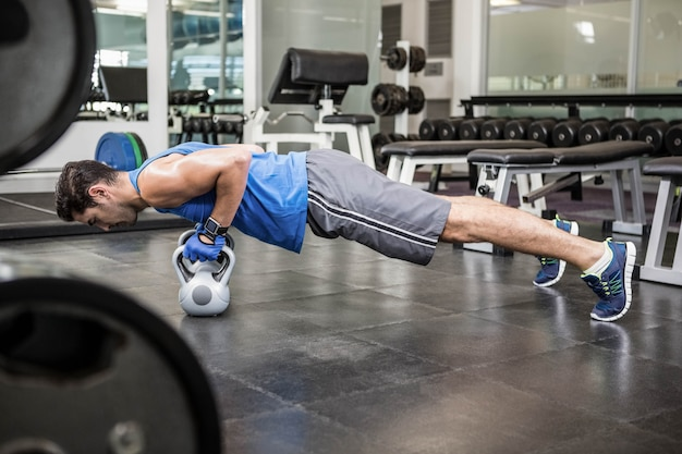 Homem musculoso fazendo push ups com kettlebells no ginásio