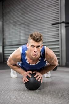 Homem musculoso fazendo puxar para cima com bola de medicina no ginásio crossfit