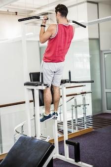 Homem musculoso fazendo puxar para cima em um ginásio