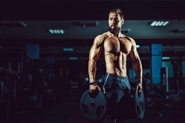Homem musculoso fisiculturista atleta posando com halteres no ginásio.