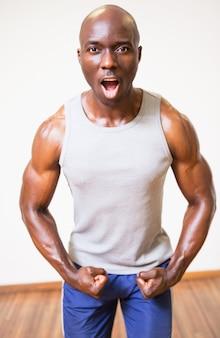 Homem musculoso gritando enquanto flexiona os músculos