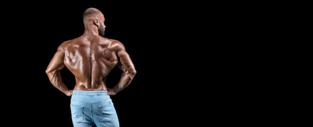 Homem musculoso isolado isolado no preto. vista traseira