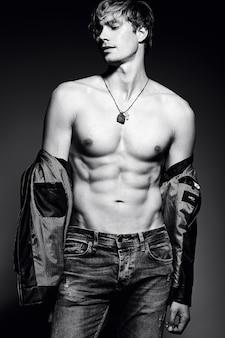 Homem musculoso jovem bonito modelo masculino apto posando no estúdio, mostrando seus músculos abdominais