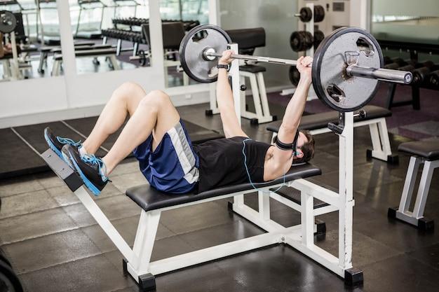 Homem musculoso, levantando a barra no banco no ginásio