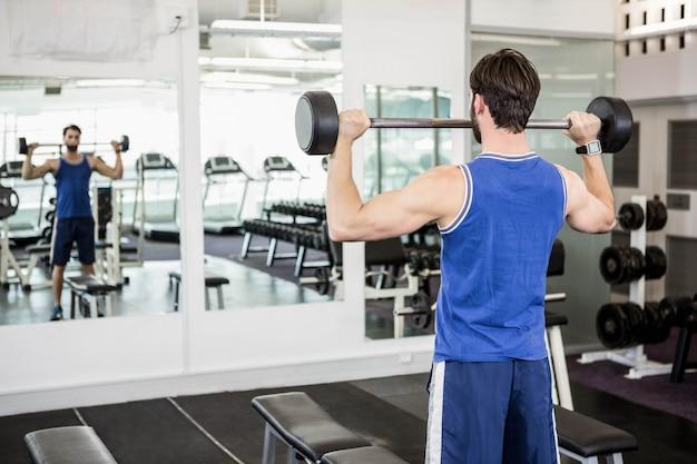 Homem musculoso, levantando a barra no ginásio