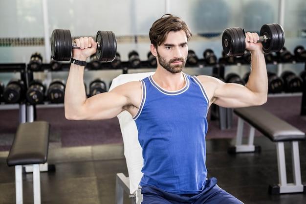 Homem musculoso levantando halteres no banco no ginásio