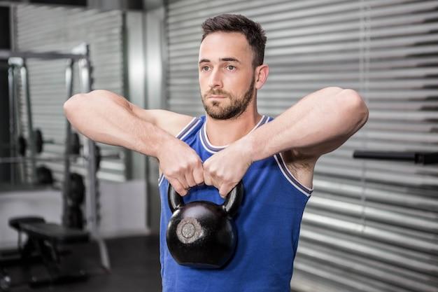 Homem musculoso, levantando o kettlebell pesado no ginásio crossfit