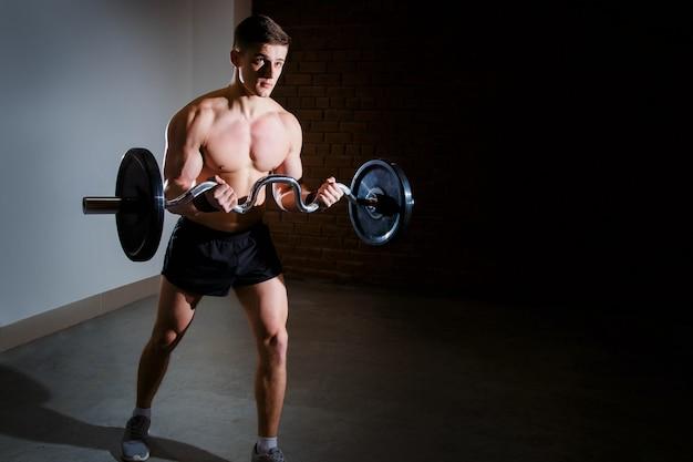 Homem musculoso malhando na academia fazendo exercícios com barra