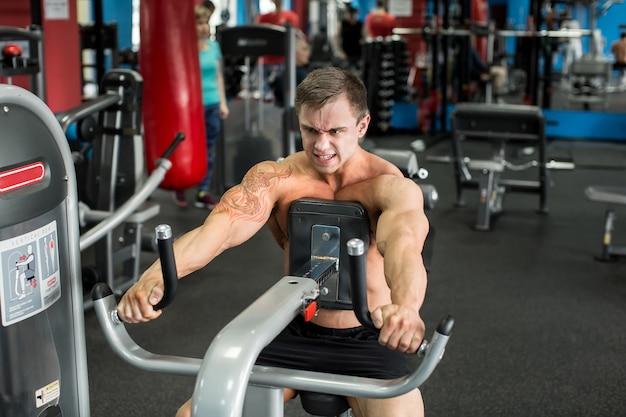 Homem musculoso malhando na academia fazendo exercícios, homem forte
