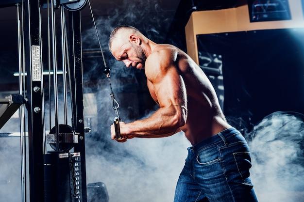 Homem musculoso malhando na academia fazendo exercícios