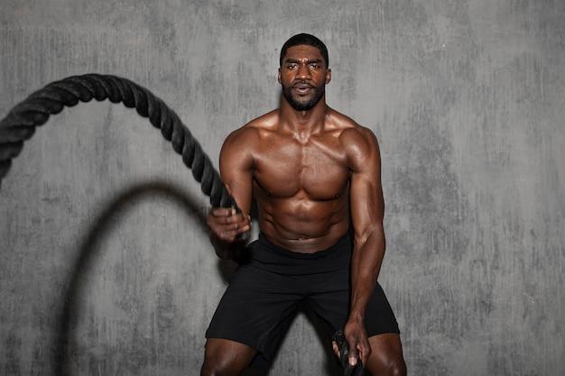 Homem musculoso malhando nas cordas de batalha em uma academia