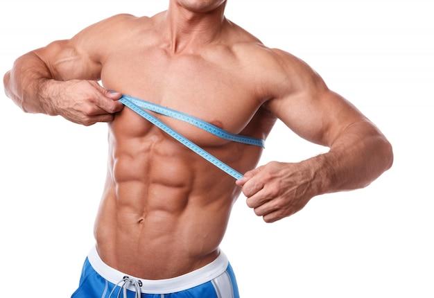 Homem musculoso, medindo o peito